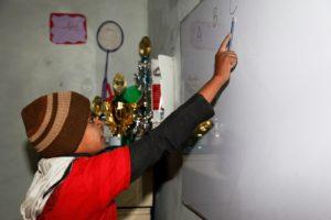 Shan schreibt im Spaß- und Lernzentrum das Aphabet an die Tafel. (Quelle: Christian Herrmanny)