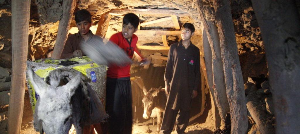 Shan und seine zwei Freunde beladen im Stollen einen Esel mit Kohle. (Quelle: Christian Herrmanny)