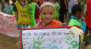 Ein Mädchen hält während einer Demonstration ein selbst gemaltes Plakat mit portugiesischer Aufschrift hoch. (Quelle: Stefanie Feuersinger)