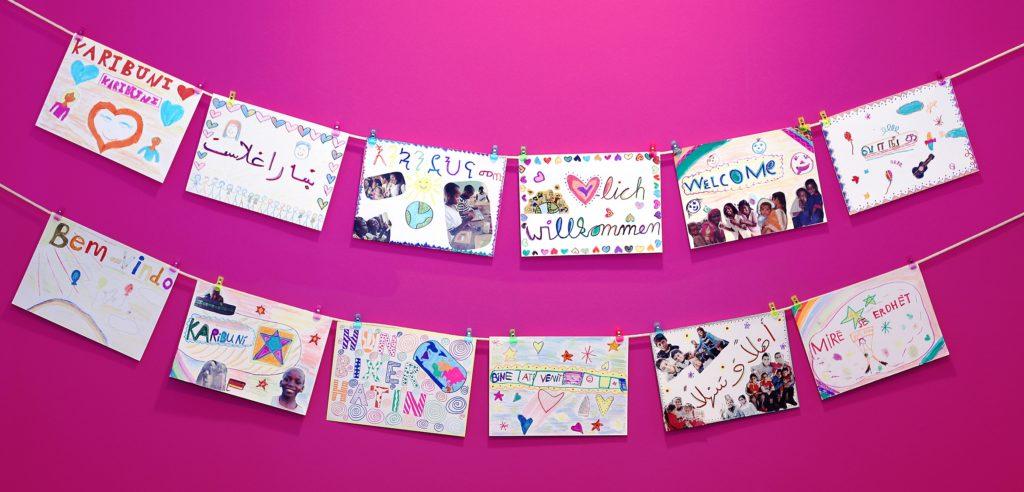 Girlande mit Herzlich-willkommen-Schildern in verschiedenen Sprachen. (Quelle: Petra Liedtke)