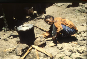Ein Mädchen kocht auf einem Drei-Steine-Ofen. (Quelle: DieterKohl)