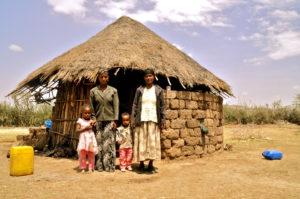 Eine Familie steht vor ihrer Hütte. (Quelle: Bastian Strauch)