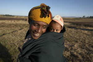 Eine Mutter trägt ihr Kind in einem Tuch auf dem Rücken. (Quelle: Frank Peterschröder)