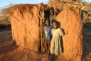 Drei Kinder stehen im Eingang einer niedrigen, baufälligen Lehmhütte. (Quelle: Ralf Krämer)