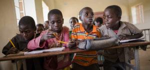 Vier Jungen quetschen sich auf einer Schulbank. (Quelle: Jakob Studnar)