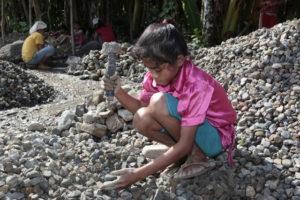 Ein Mädchen zerklopft Steine. (Quelle: Christian Herrmanny)