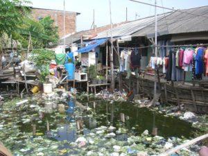 Hütten an einem mit Müll verschmutzten Fluss. (Quelle: Martina Kiese)