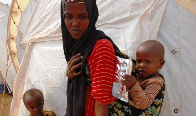 Ein Mädchen in einem Flüchtlingslager trägt ein Baby auf dem Rücken. Quelle: Dietmar Roller