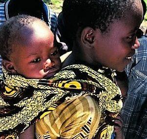 Ein Mädchen trägt sein Geschwisterchen in einem Kanga auf dem Rücken. (Quelle: Ralf Krämer)