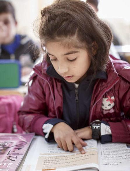Ein syrisches Mädchen liest in einem Schulbuch. (quelle: Jakob Studnar)