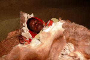 Tafari schläft auf dem Boden unter einem Tierfell. (Quelle: Christian Herrmanny)