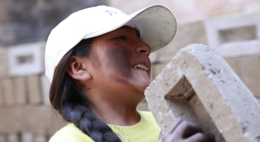 Margarita schleppt einen schweren Ziegelstein. (Quelle: Christian Herrmanny)