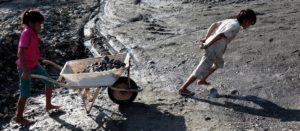 Yeni schiebt eine Schubkarre voller Steine, während ein Junge von vorne zieht. (Quelle: Christian Herrmanny)