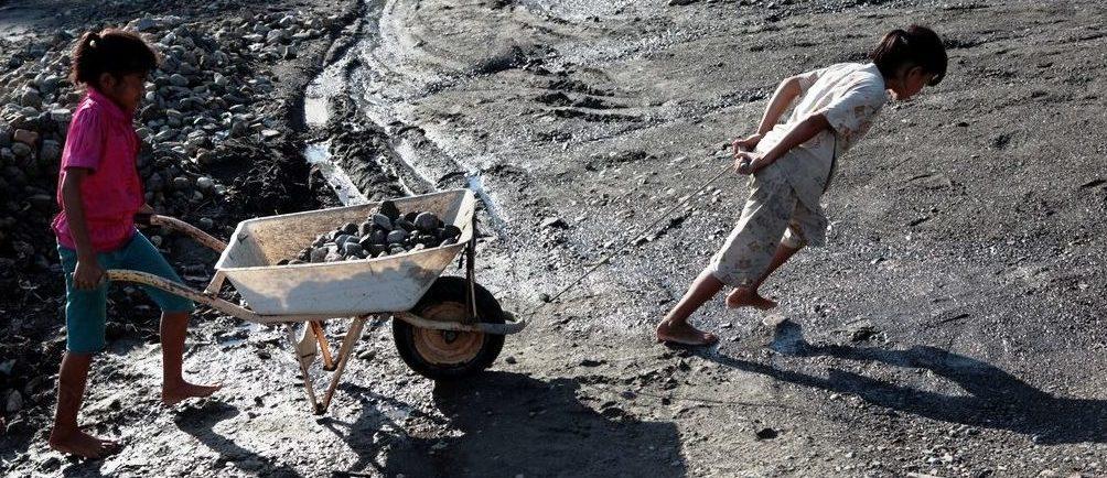 Zwei indonesische Kinder schieben/ziehen eine schwere Schubkarre mit Steinen. (Quelle: Christian Herrmanny)