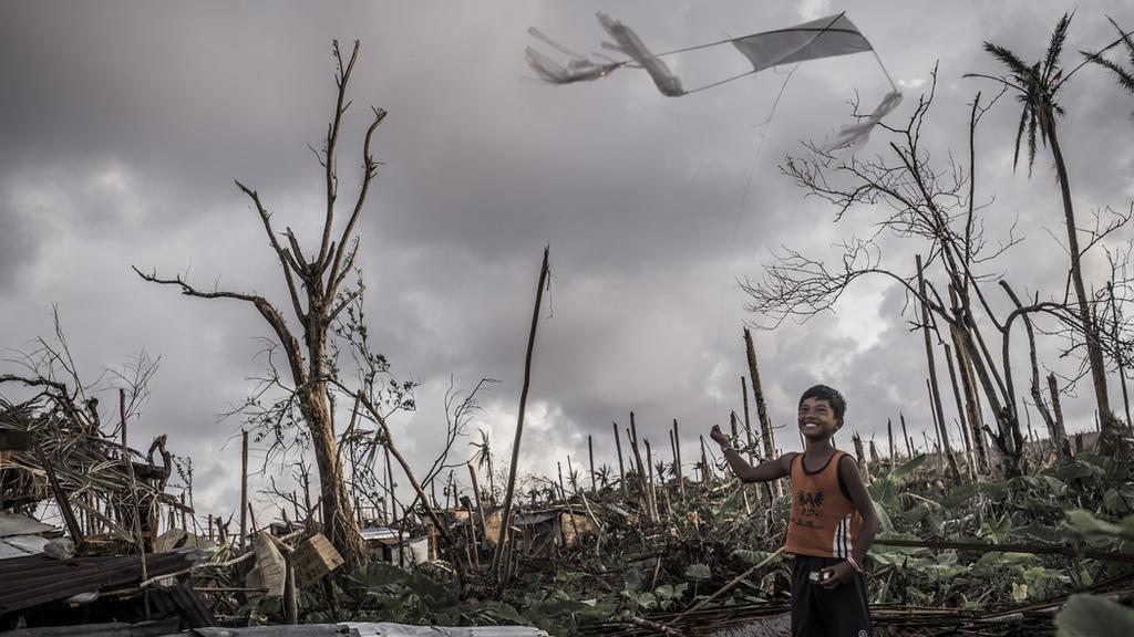 Nach dem Taifun Haiyan spielt ein Jungen in seinem zerstörten Dorf mit seinem Drachen. (Quelle: Jakob Studnar)