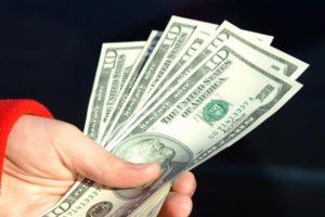 Eine Hand hält Dollar-Scheine. (Quelle: FreeFoto.com)