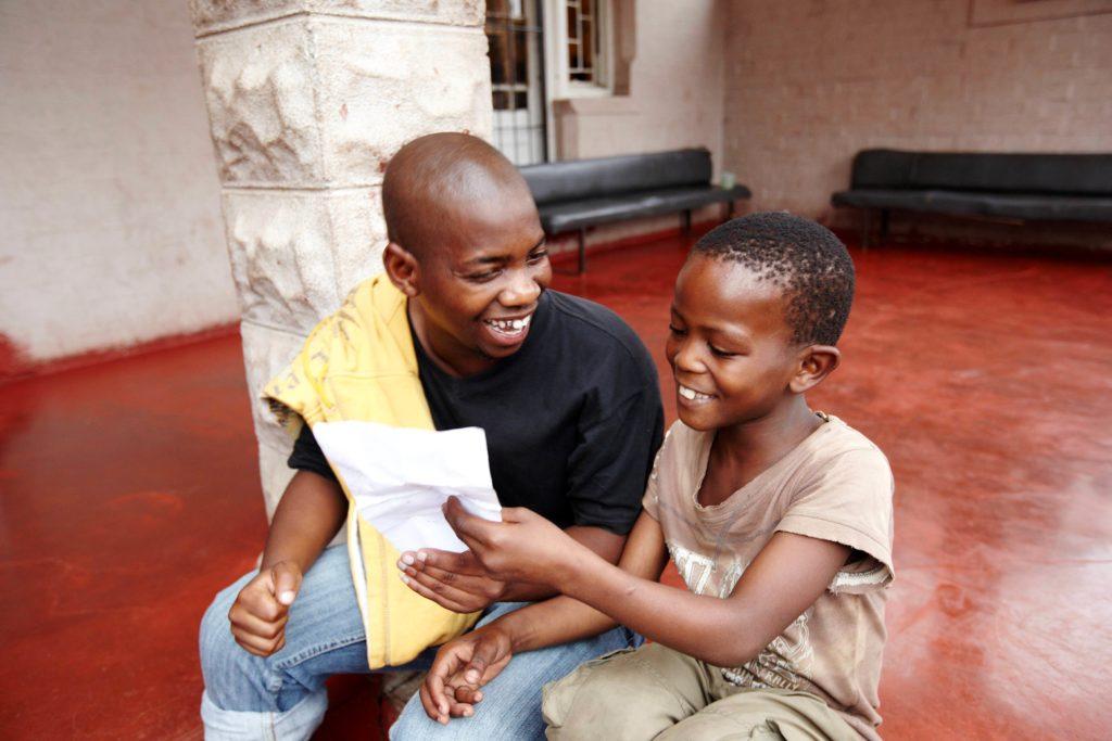 Ein Mitarbeiter in einem Straßenkinderprojekt in Südafrika übt mit einem Jungen Lesen. (Quelle: Frank Peterschröder)