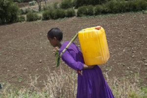 Das äthiopische Mädchen hat jedes Mal Rückenschmerzen, wenn es über viele Stunden den schweren Wasserkanister geschleppt hat. (Quelle: Christian Herrmanny)
