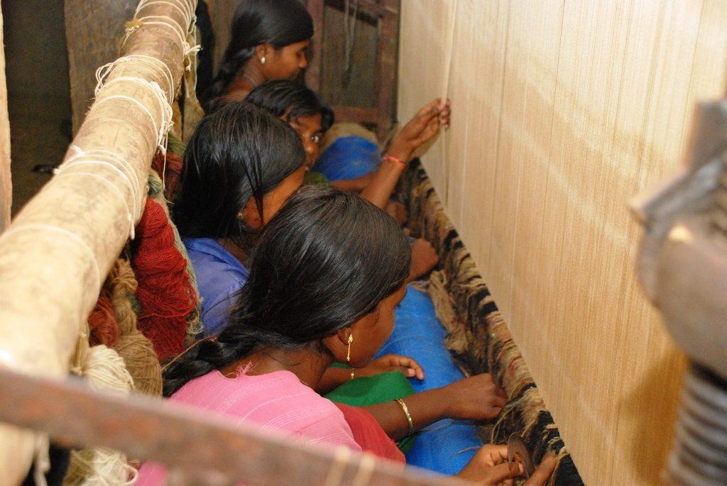 Mädchen sitzen ganz eng zusammengepfercht an einem Webstuhl. (Quelle: Kindernothilfe-Partner)