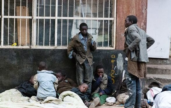 Straßenkinder liegen auf Pappe und Decken vor einem vergitterten Haus. (Quelle: Boland Brockmann)