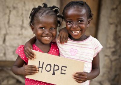 """Zwei Mädchen halten ein Schild mit dem Wort """"Hope"""" (Hoffnung) vor sich. (Quelle: iStock)"""