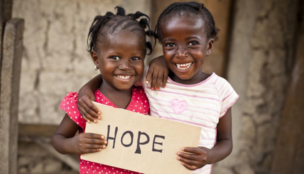 """Zwei kenianische Mädchen halten ein Schild mit dem Wort """"Hope"""". (Quelle: MShep2/iStock)"""