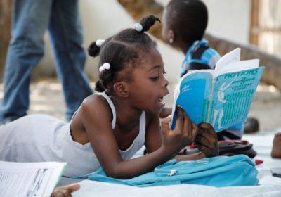 Ein Mädchen liegt auf dem Boden und liest ein Buch. (Quelle: Jürgen Schübelin)