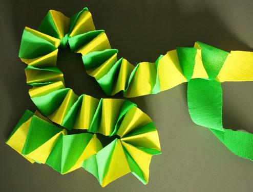 Eine gelbgrüne Girlande aus zwei Streifen Krepppapier. (Quelle: Yo.Ko.Graphics)