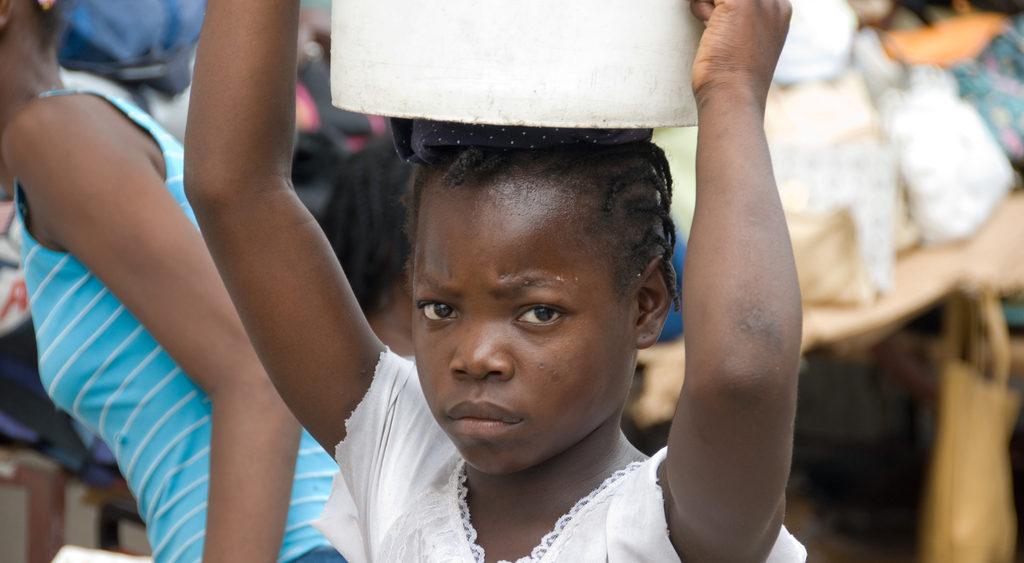 Ein Restavèk-Mädchen trägt einen Eimer auf dem Kopf. (Quelle: Dietmar Roller)