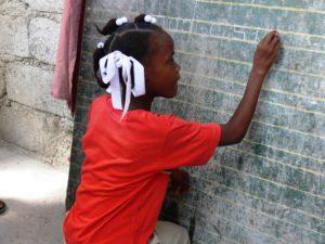 Restavèk-Mädchen schreibt etwas an die Tafel. (Quelle: Maike Ewuntomah)