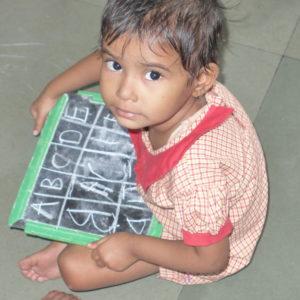 Ein Kind mit einer Schultafel. (Quelle: Guido Falkenberg)