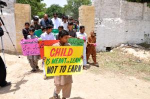 """Kinder protestieren mit Plakaten gegen Kinderarbeit. """"Ein Kind soll lernen, nicht Geld verdienen"""". (Quelle: Kindernothilfe-Partner)"""