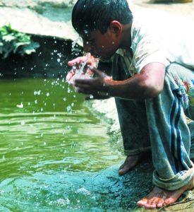 Ein Junge trinkt Wasser aus einem Fluss. (Quelle: Jens Großmann)