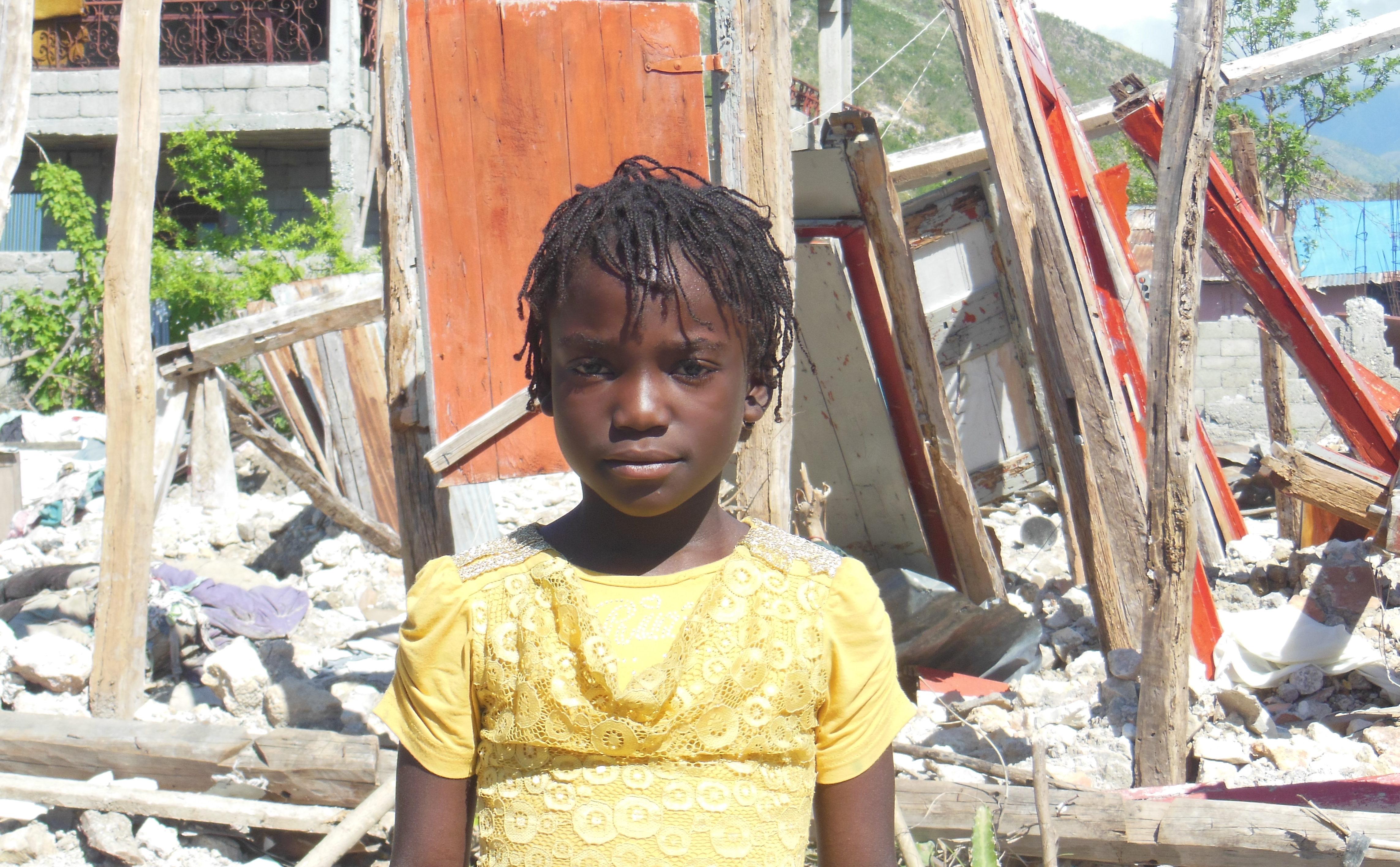 Ein Mädchen vor den Trümmern ihres Hauses in Haiti. (Quelle: Kindernothilfe-Partner)