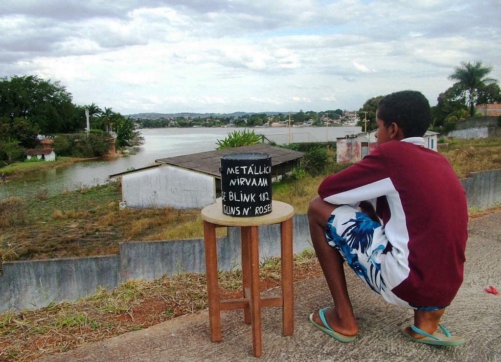 Ein Junge hockt neben seiner Dosenkamera und blickt über einen Fluss. (Quelle: Jürgen Schübelin)