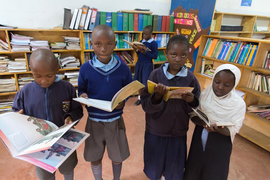 Kinder mit Büchern in einer Bibliothek. (Quelle: Stefan Trappe)