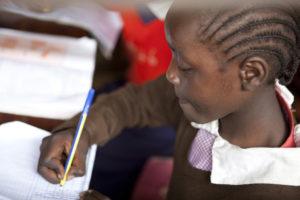 Ein Mädchen schreibt etwas in ein Heft. (Quelle: Frank Rothe)