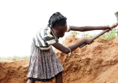Ein Mädchen schaufelt Sand in einem Sandbruch. (Quelle: Christian Herrmanny)