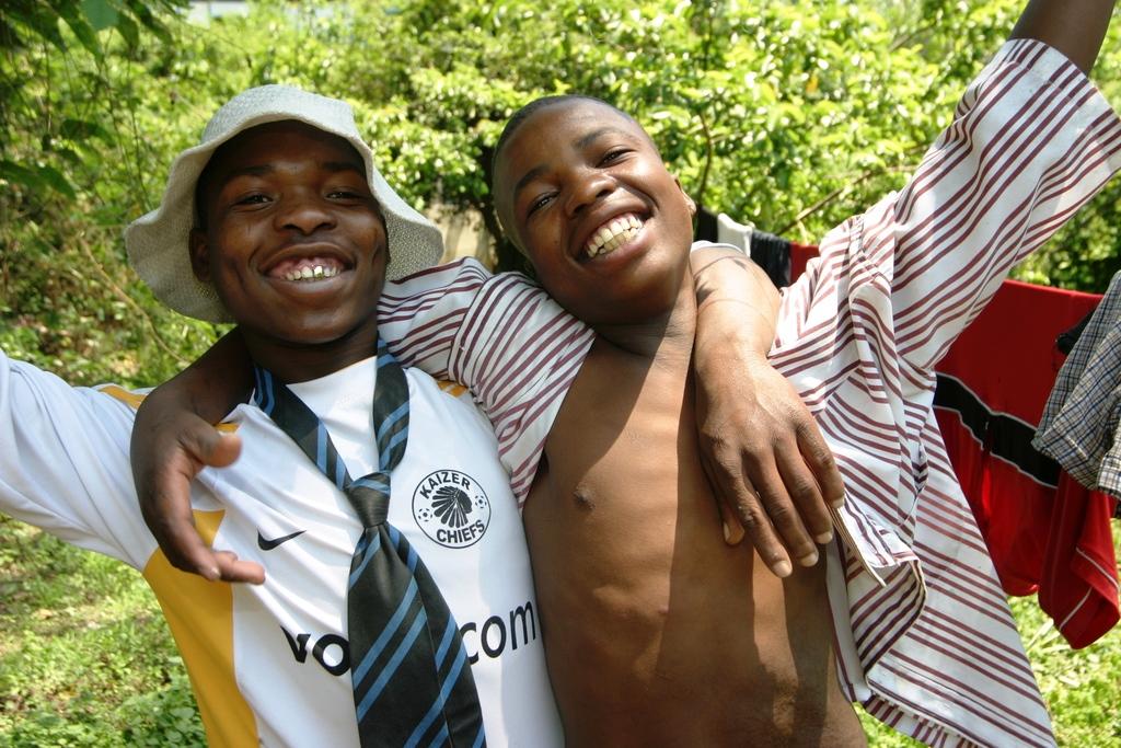 Zwei lachende südafrikanische Straßenjungen, einer von ihnen trägt eine Krawatte. (Quelle: Ralf Krämer)