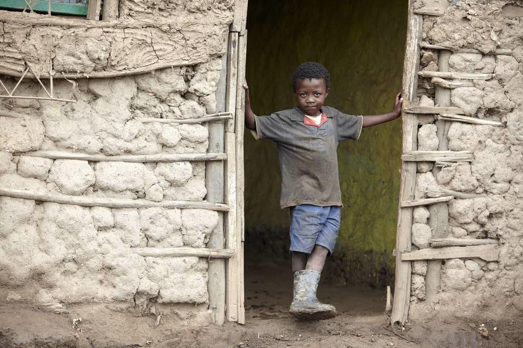 Ein Junge steht in der Tür eines Lehmhauses. (Quelle: Peterschröder)
