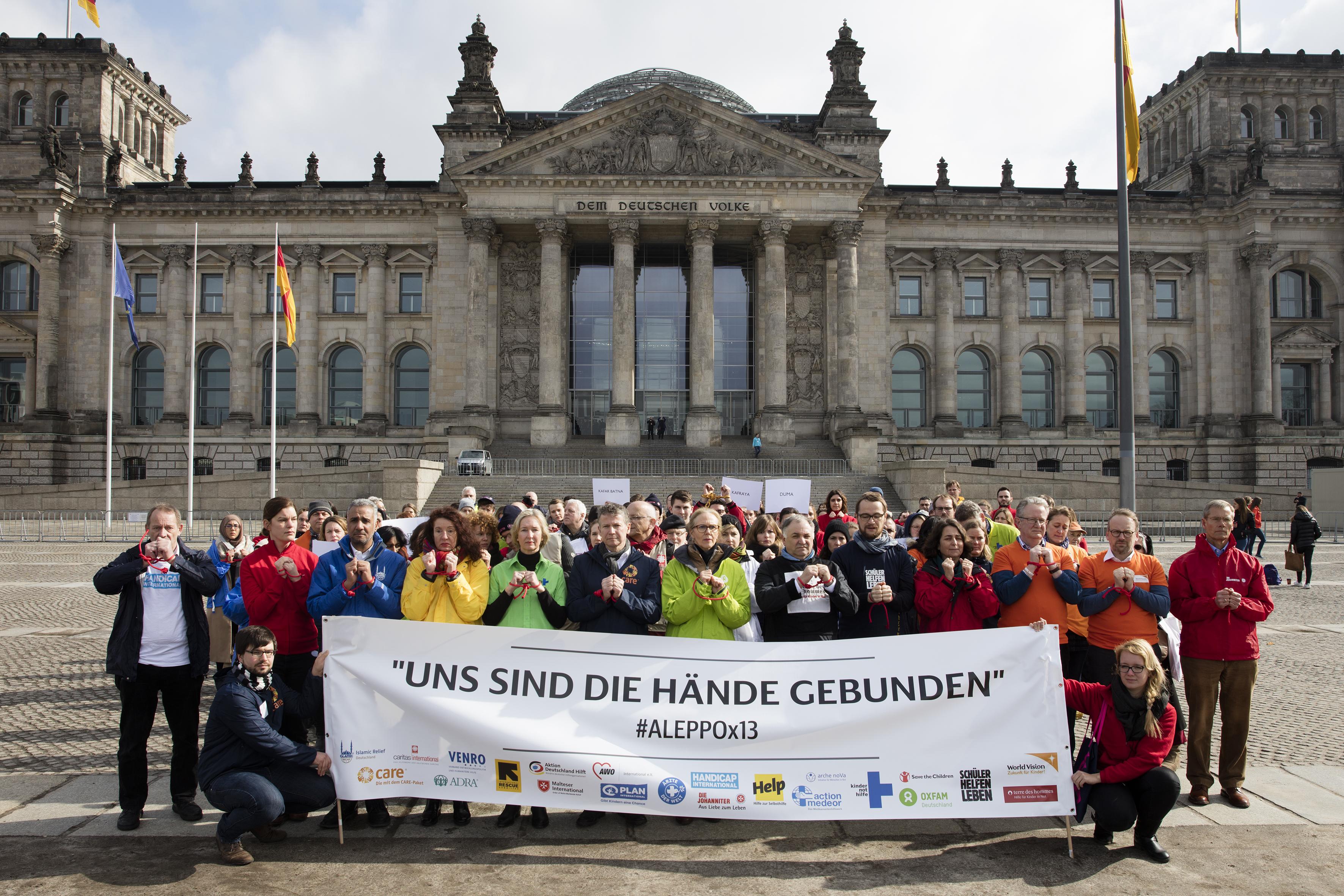 Vertreter von deutschen Hilfswerken stehen mit gebundenen Händen vor dem Bundestag in Berlin. (Quelle: Mike Auerbach)