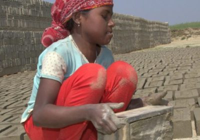 Ein Mädchen hebt eine Ziegelform hoch. (Quelle: Malte Pfau)