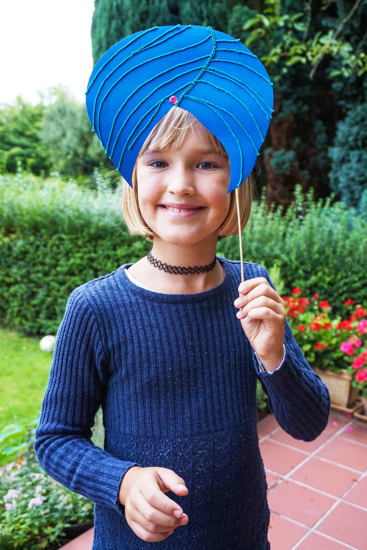 Ein Mädchen hält sich einen Turban aus blauem Tonpapier vor den Kopf. (Quelle: Ralf Krämer)