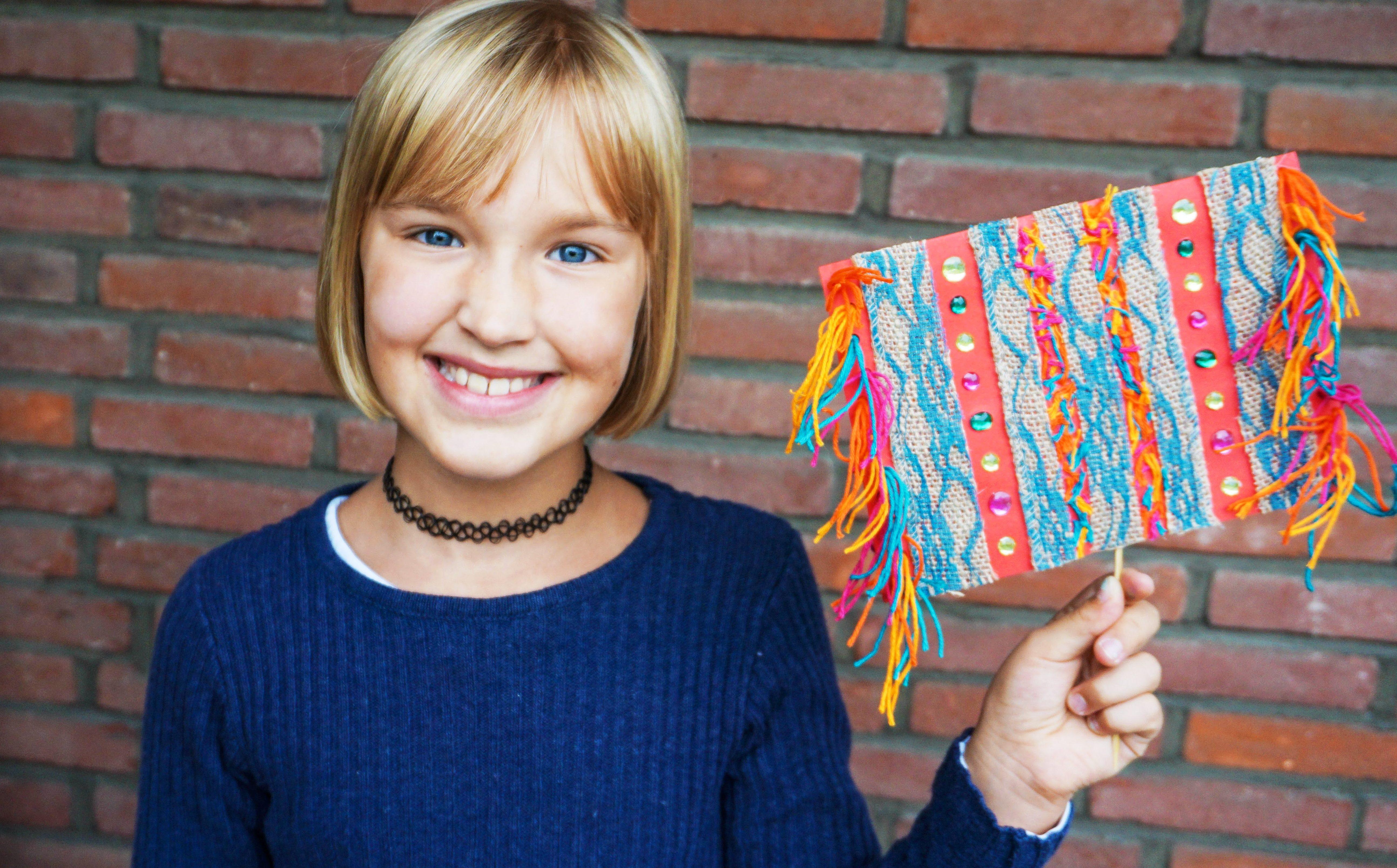 Ein Mädchen hält ein Stück Fransenteppich aus Tonpapier, Borte und Wolle hoch. (Quelle: Ralf Krämer)