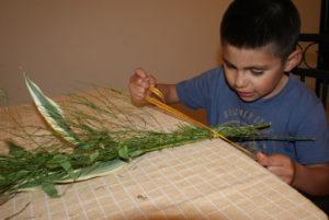 Ein Junge aus Ecuador knotet Zweige zu einem Strauß zusammen. (Quelle: Kindernothilfe-Partner)