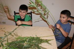 Zwei Jungen aus Ecuador binden Zweige zu Sträußen zusammen. (Quelle: Kindernothilfe-Partner)