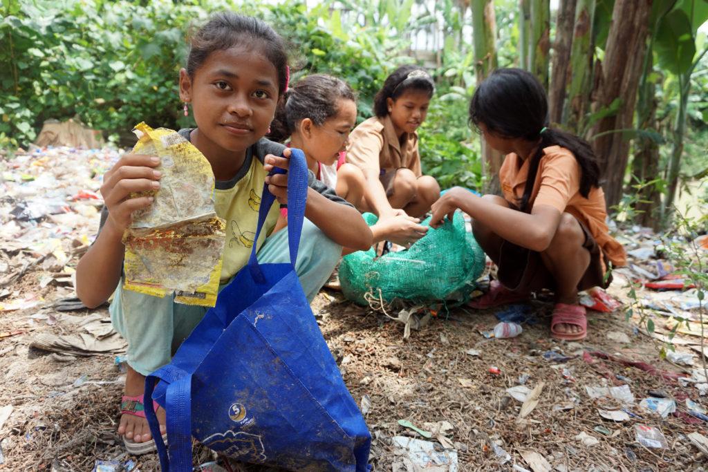 4 Mädchen hocken in einem Wald auf dem Boden und sammeln Müll, der überall herumliegt