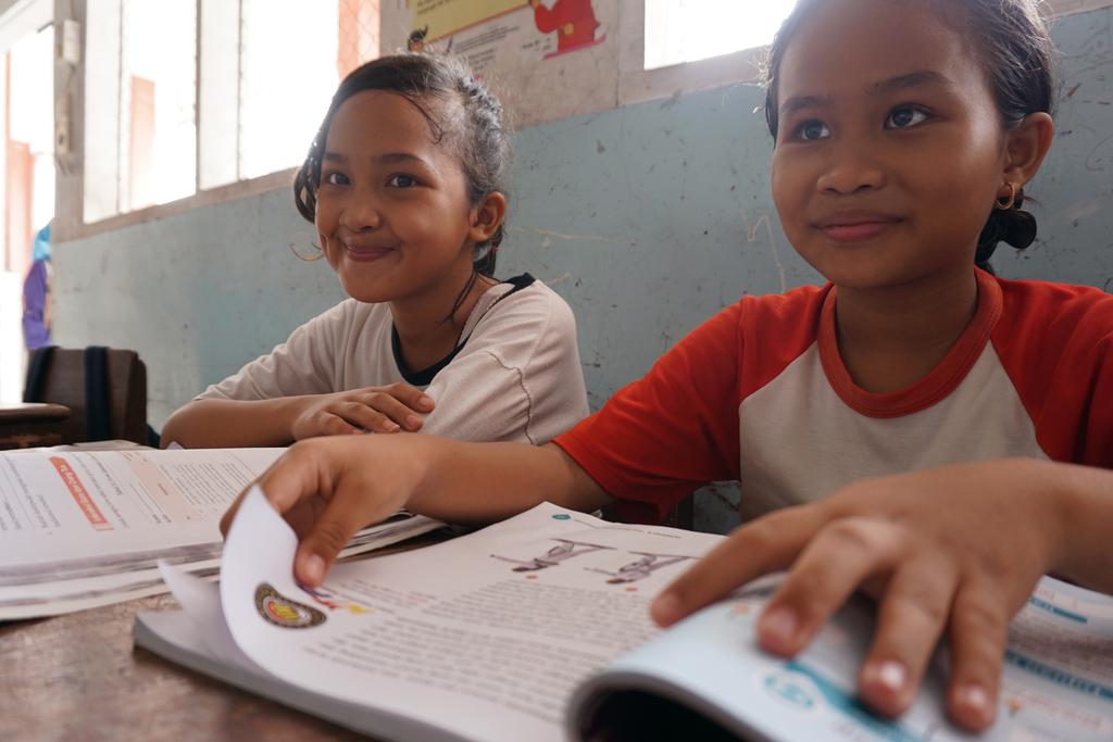 Zwei Mädchen sitzen im Klassenzimmer mit aufgeschlagenen Büchern vor sich