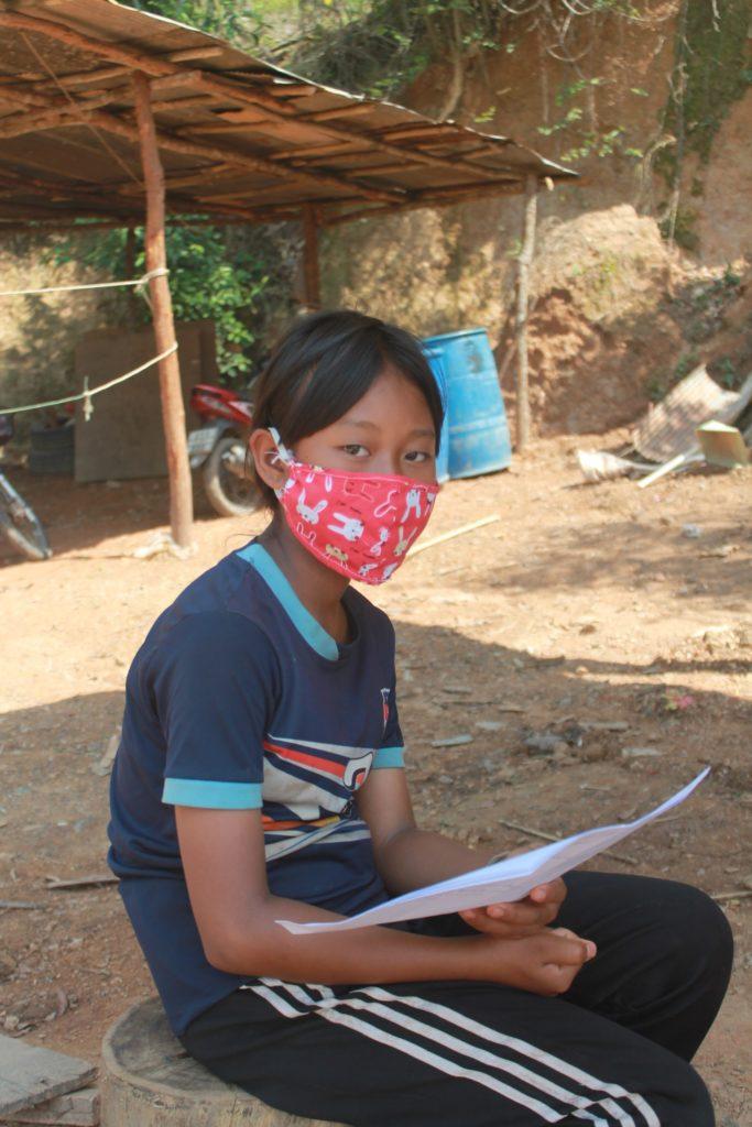 Aung sitzt draußen im Hof. Sie trägt eine rote Maske mit weißen Hasenköpfen darauf. (Quelle: Kindernothilfe-Partner APCYF)