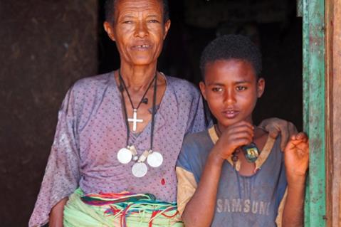 Ein Junge und die Frau, die ihn gekauft hat, stehen in einem Eingang (Quelle: Malte Pfau)